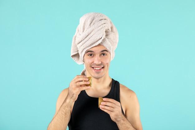 Vorderansicht des jungen mannes nach der dusche mit kiwischeiben an blauer wand
