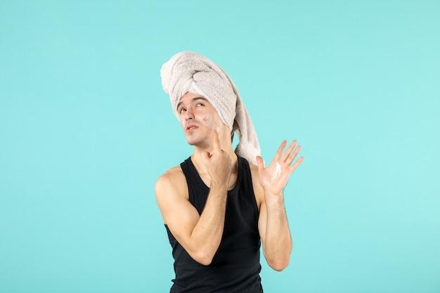 Vorderansicht des jungen mannes nach der dusche mit sahne im gesicht an der blauen wand
