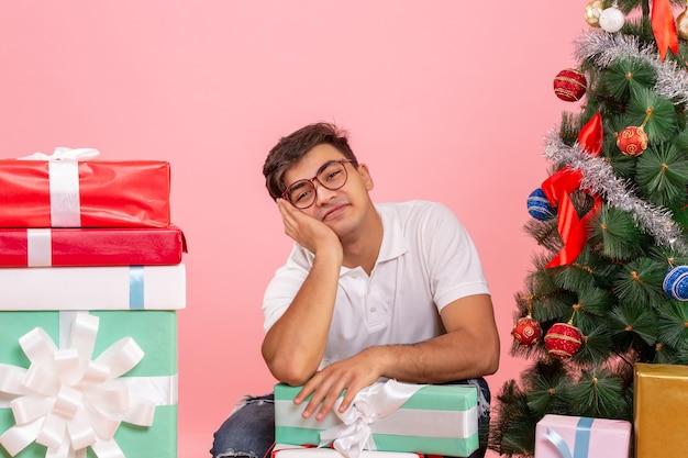 Vorderansicht des jungen mannes um geschenke und weihnachtsbaum an der rosa wand
