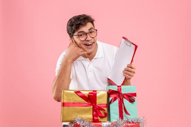 Vorderansicht des jungen mannes um weihnachten präsentiert das halten der aktennotiz an der rosa wand