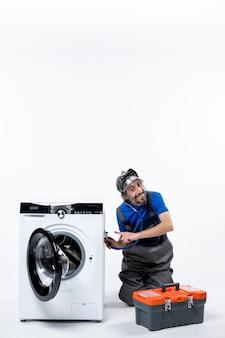 Vorderansicht des jungen mechanikers, der das stethoskop auf die waschmaschine setzt, die in der nähe der waschmaschinenwerkzeugtasche auf weißem grund sitzt