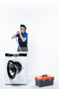 Vorderansicht des jungen mechanikers in uniform, der hinter der waschmaschine steht und das rohr an der weißen wand ausbläst