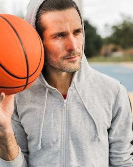 Vorderansicht des jungen mit basketballball
