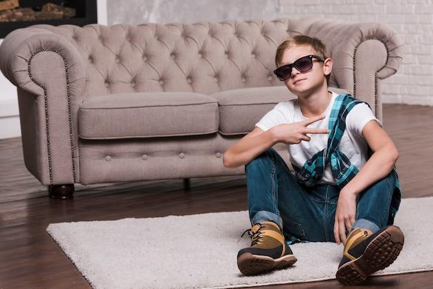Vorderansicht des jungen mit der sonnenbrille, die auf boden sitzt