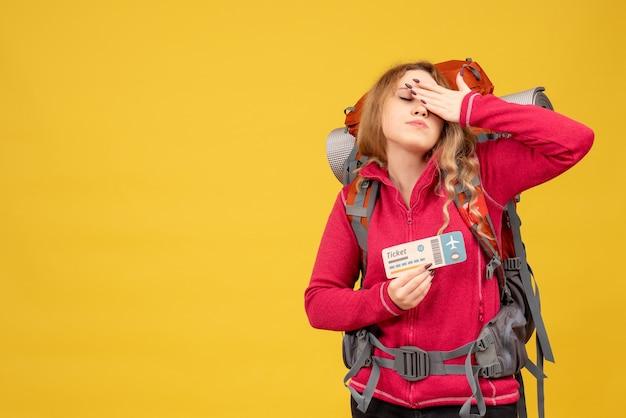 Vorderansicht des jungen müden reisenden mädchens in der medizinischen maske, die ticket hält