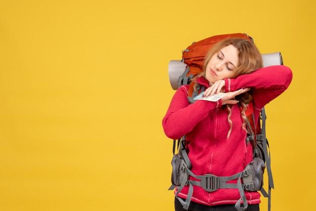 Vorderansicht des jungen schläfrigen reisenden mädchens in der medizinischen maske, die ticket hält