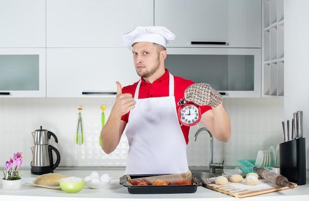Vorderansicht des jungen selbstbewussten männlichen kochs, der einen halter mit einer uhr trägt und in der weißen küche eine gute geste macht