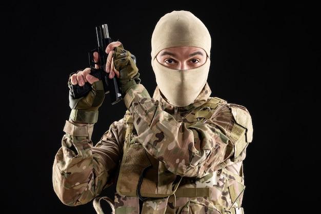 Vorderansicht des jungen soldaten in einheitlicher nachladepistole auf schwarzer wand