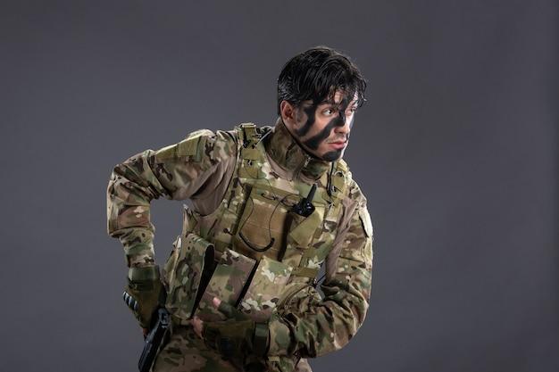 Vorderansicht des jungen soldaten in tarnung mit pistole an der dunklen wand