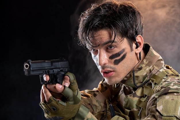 Vorderansicht des jungen soldaten in tarnung mit pistole auf schwarzer wand