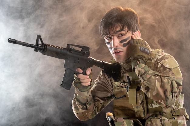 Vorderansicht des jungen soldaten in tarnung mit schwarzer wand des maschinengewehrs