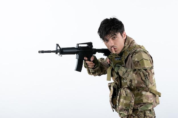Vorderansicht des jungen soldaten in tarnung mit weißer wand des maschinengewehrs