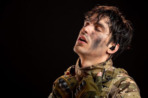 Vorderansicht des jungen soldaten in uniform an dunkler wand