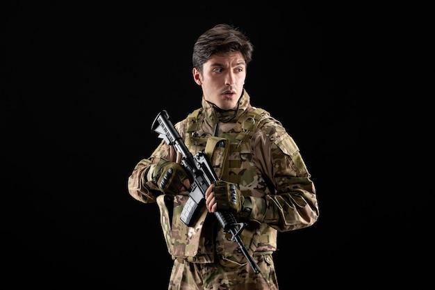 Vorderansicht des jungen soldaten in uniform mit gewehr auf schwarzer wand
