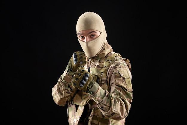 Vorderansicht des jungen soldaten in uniform und handschuhen an schwarzer wand