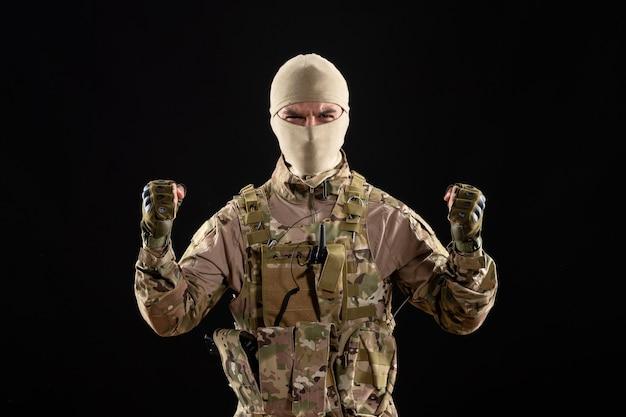 Vorderansicht des jungen soldaten in uniform und maske auf schwarzer wand