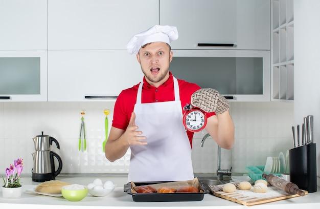 Vorderansicht des jungen überraschten männlichen kochs, der einen halter mit einer uhr trägt und eine ok geste in der weißen küche macht