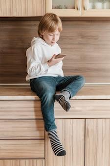 Vorderansicht des jungen unter verwendung des smartphones