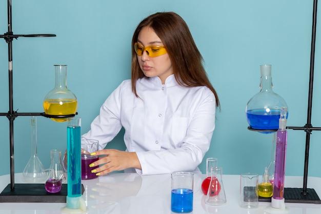 Vorderansicht des jungen weiblichen chemikers im weißen anzug vor dem tisch, der mit lösungen arbeitet