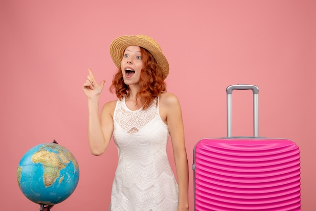 Vorderansicht des jungen weiblichen touristen mit rosa tasche auf rosa wand