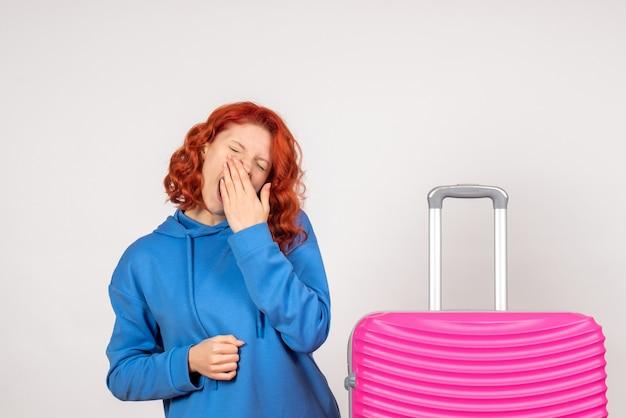 Vorderansicht des jungen weiblichen touristen mit rosa tasche auf weißer wand
