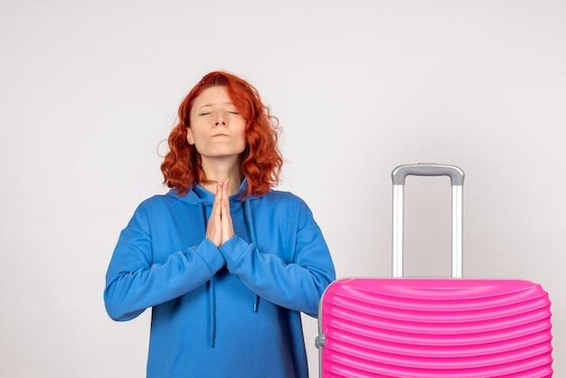 Vorderansicht des jungen weiblichen touristen mit rosa tasche, die auf weißer wand betet