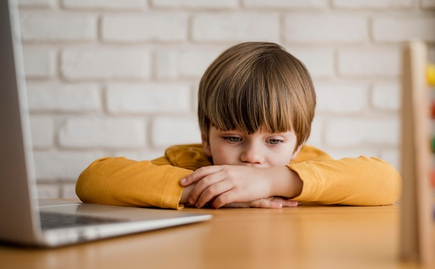 Vorderansicht des kindes am schreibtisch, das mit laptop studiert