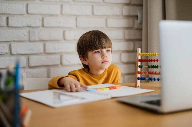 Vorderansicht des kindes am schreibtisch, das vom laptop lernt