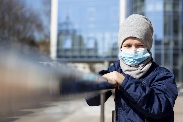 Vorderansicht des kindes, das außerhalb mit medizinischer maske aufwirft