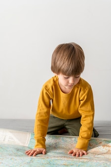 Vorderansicht des kindes, das karte zu hause betrachtet