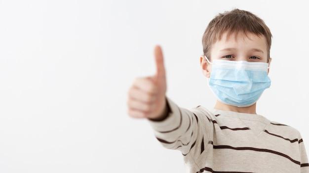 Vorderansicht des kindes, das medizinische maske trägt, die daumen aufgibt