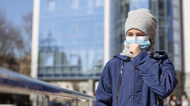 Vorderansicht des kindes, das medizinische maske und husten trägt