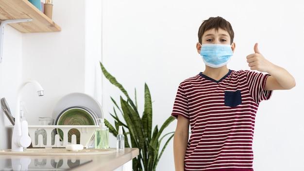 Vorderansicht des kindes mit der medizinischen maske, die daumen aufgibt