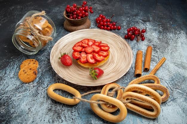 Vorderansicht des kleinen fruchtigen kuchens mit crackern auf dunkler oberfläche