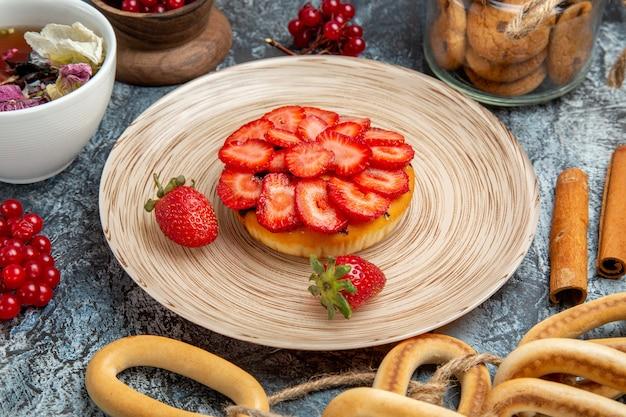 Vorderansicht des kleinen fruchtigen kuchens mit tee auf dunkler oberfläche