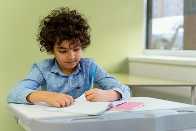 Vorderansicht des kleinen jungen in der klasse an der schule
