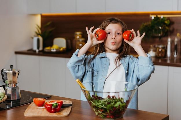 Vorderansicht des kleinen mädchens in der küche, die spaß mit gemüse hat