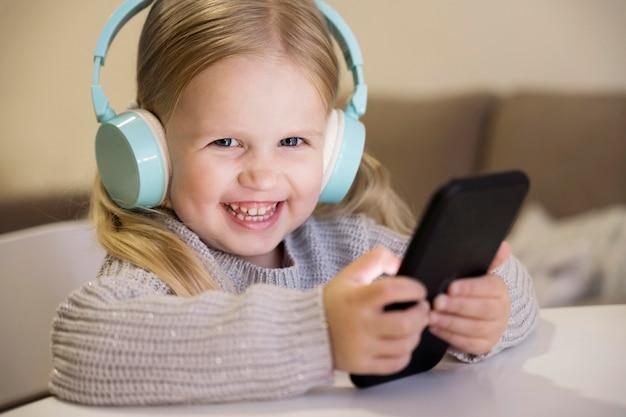 Vorderansicht des kleinen mädchens mit kopfhörern und telefon