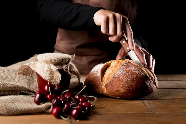 Vorderansicht des kochs, der brot mit glas kirschmarmelade schneidet