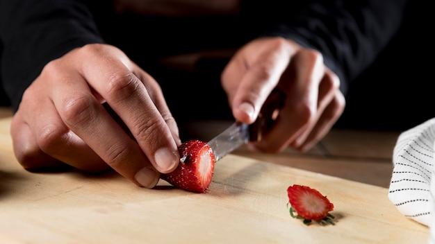 Vorderansicht des kochs, der erdbeere hackt