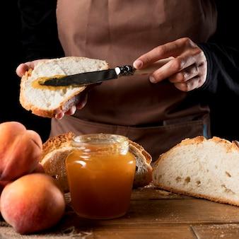 Vorderansicht des kochs, der pfirsichmarmelade auf brot verteilt