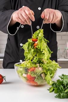 Vorderansicht des kochs, der salat wirft