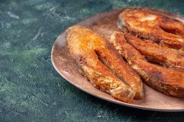 Vorderansicht des köstlichen gebratenen fisches auf einem braunen teller auf der linken seite auf mischfarbtabelle mit freiem raum