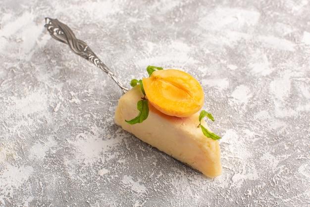 Vorderansicht des köstlichen kuchenstücks mit aprikosenscheibe auf dem hellen schreibtisch