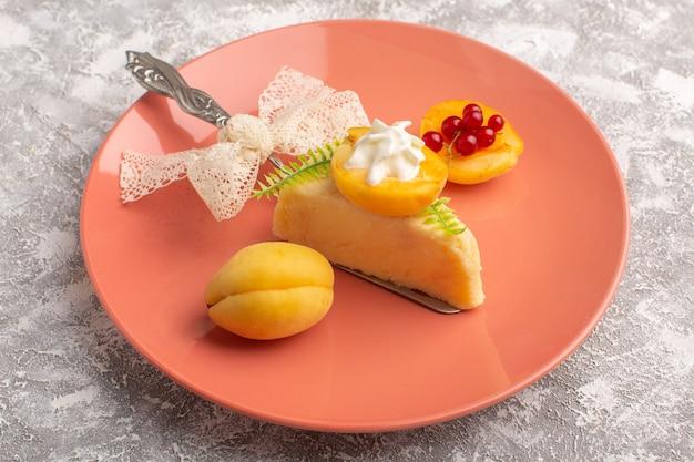 Vorderansicht des köstlichen kuchenstücks mit sahne und frischen aprikosen innerhalb des rosa tellers auf dem hellen schreibtisch