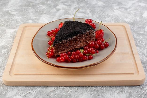 Vorderansicht des köstlichen schokoladenkuchens, der mit schokocreme und frischen roten preiselbeeren auf dem hölzernen schreibtisch geschnitten wird