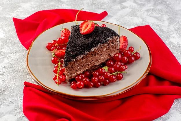 Vorderansicht des köstlichen schokoladenkuchens, der mit schokoladencreme und frischen roten preiselbeeren geschnitten wird