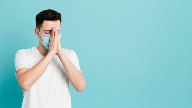 Vorderansicht des kranken mannes mit der medizinischen maske, die betet