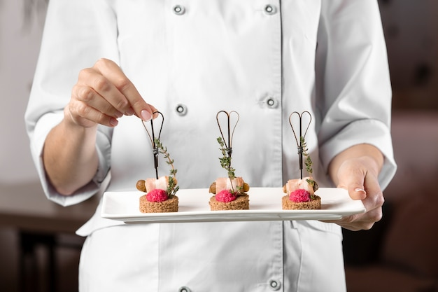 Vorderansicht des küchenchefs, der einen nahrungsmittelteller hält