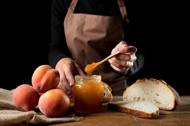 Vorderansicht des küchenchefs mit glas pfirsichmarmelade